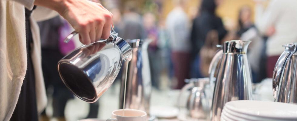 En person i en möteslokal häller upp kaffe i en kopp