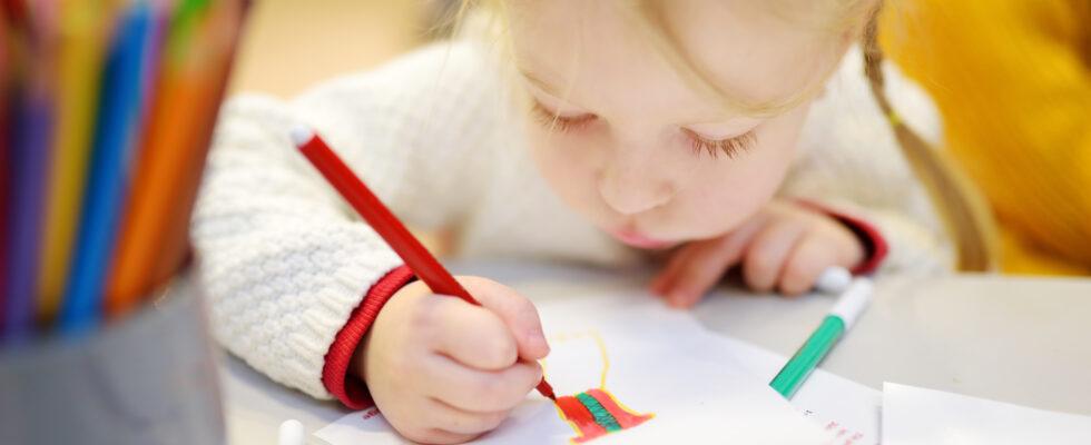 En liten flicka ritar med tuschpennor.