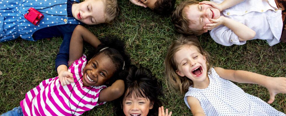 En grupp glada barn ligger på rygg i gräset.