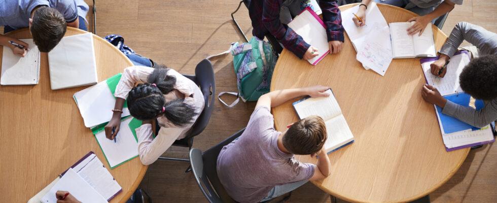 Elever sitter vid runda bord och studerar.