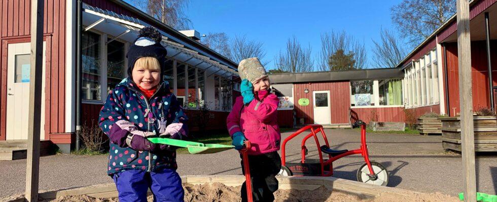 Två barn leker i sandlådan framför Kråkbackens förskola.