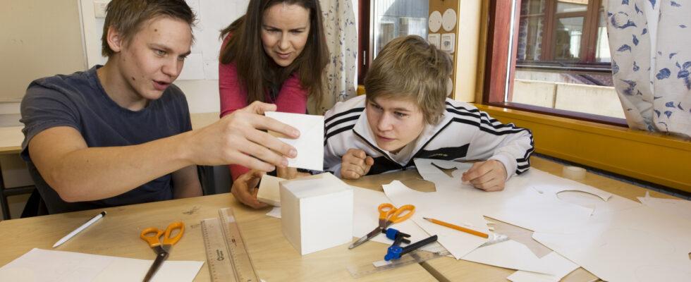 Två elever och en lärare hjälps åt med en skoluppgift.