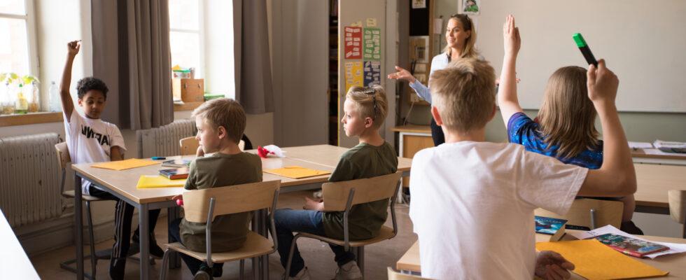 Elever i ett klassrum räcker upp handen och vill svara på lärarens frågor.enom att räcka