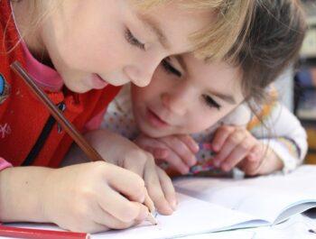 Två barn skriver i en skrivbok